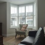 Angled Bay Window In Lounge With White Shutter Blinds