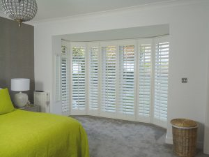 White Shutters Across Curved Patio Doors In Bedroom