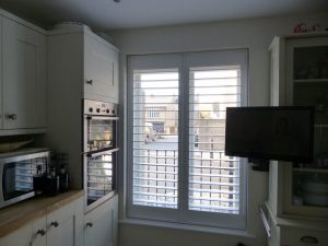 Full Height Plantation Shutters In Window Next To Kitchen Oven