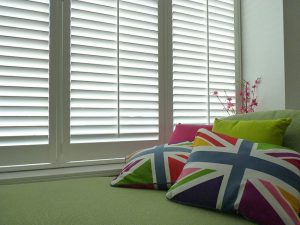 Multi-Coloured Union Jack Cushions Laying In Front Of White Window Shutters