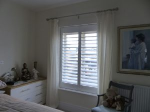 White Window Shutters In Bedroom With Sheer Cream Curtains
