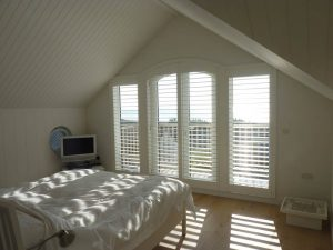 Large White Window Shutters Across Arched Balcony Doors