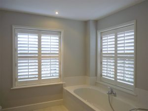 Two Large Bathroom Windows With White Shutter Blinds