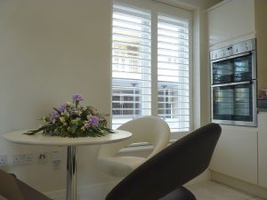 White Plantation Shutters With Big Louvre Blades In Kitchen Window