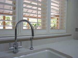 White Shutter Blinds Behind Kitchen Sink