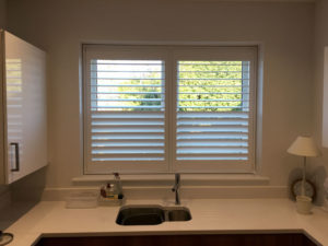 Full Height White Shutters Above Sink In Kitchen