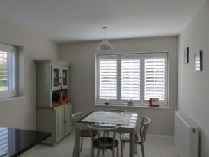 White Plantation Shutters Across Two Windows In Kitchen Diner