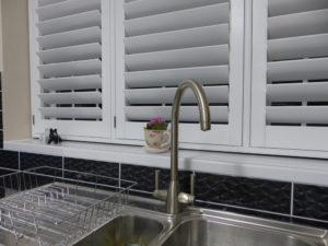 White Shutters On Window Above Sink In Kitchen