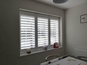 White Shutter Blinds In Three Panel Window In Dining Room