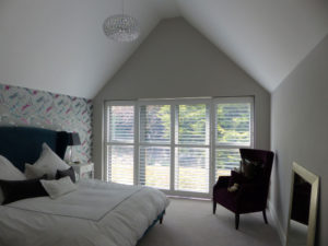 White Shutters Across Large Patio Doors In Bedroom