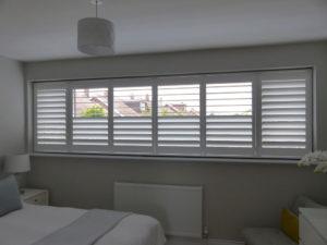 White Plantation Shutters In Bedroom With Split Tilt In Middle Panels