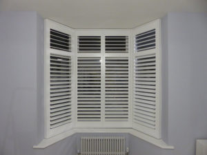 Tall Angled Bay Window With White Shutters