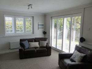 White Shutters In Shallow angled Bay Window and French Doors In Living Room
