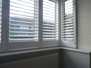 Close Up Of White Shutters In Square Bay Window