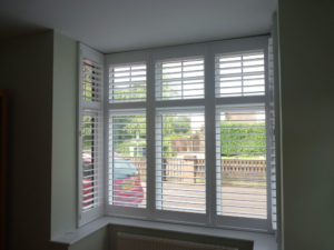 White Wooden Shutters In Square Bay Window