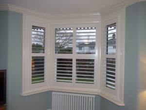 White Plantation Shutters In Angled Bay Window