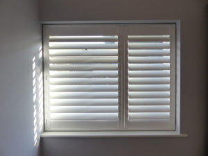 White Plantation Shutters With One Wide Panel And One Slim