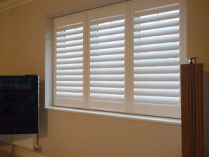White Wooden Shutters In Three Panel Window
